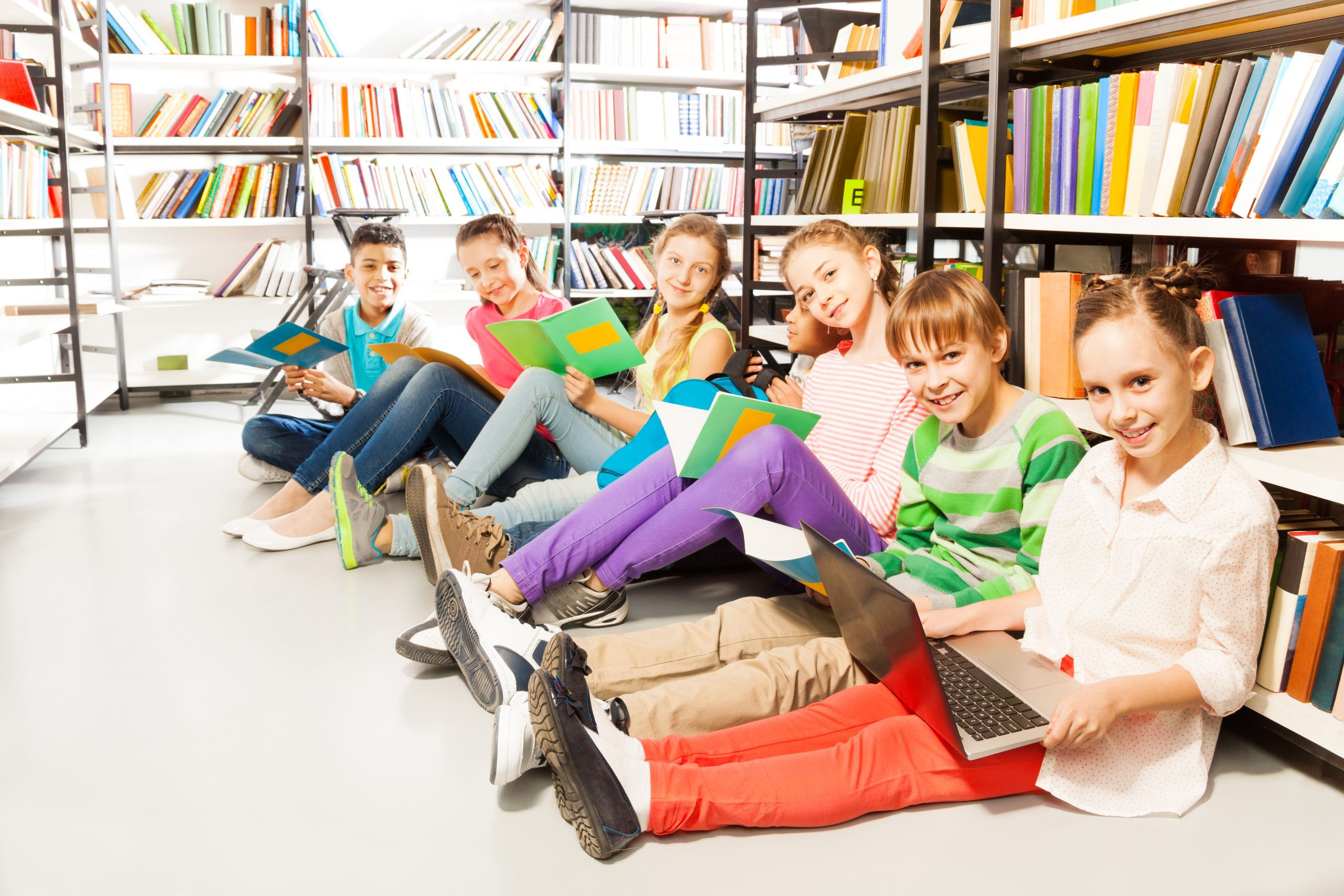Six smiling children sitting in a row on floor in the library near bookshelf and looking straight